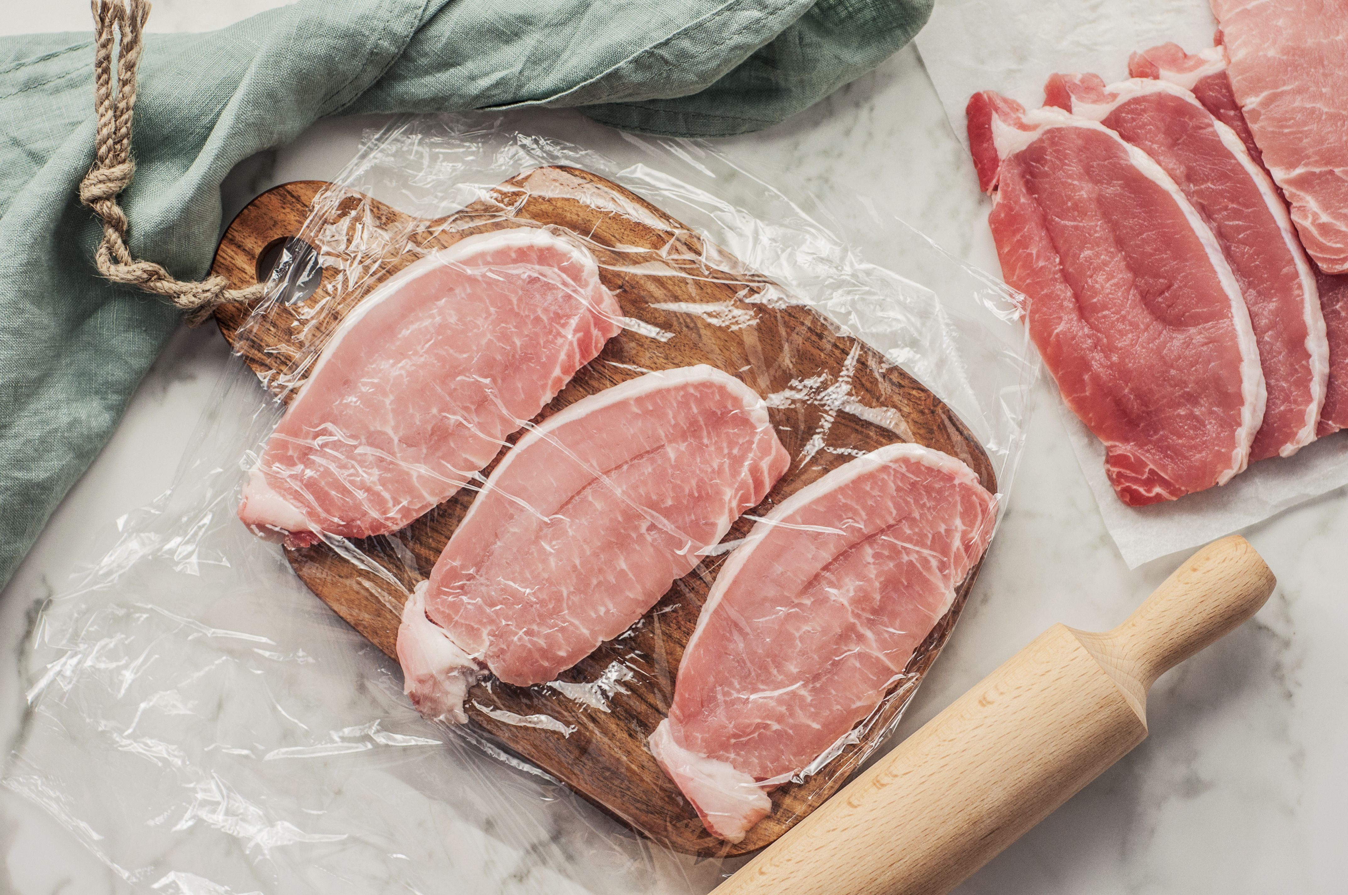 Cutlets wrapped in plastic and rolling pin
