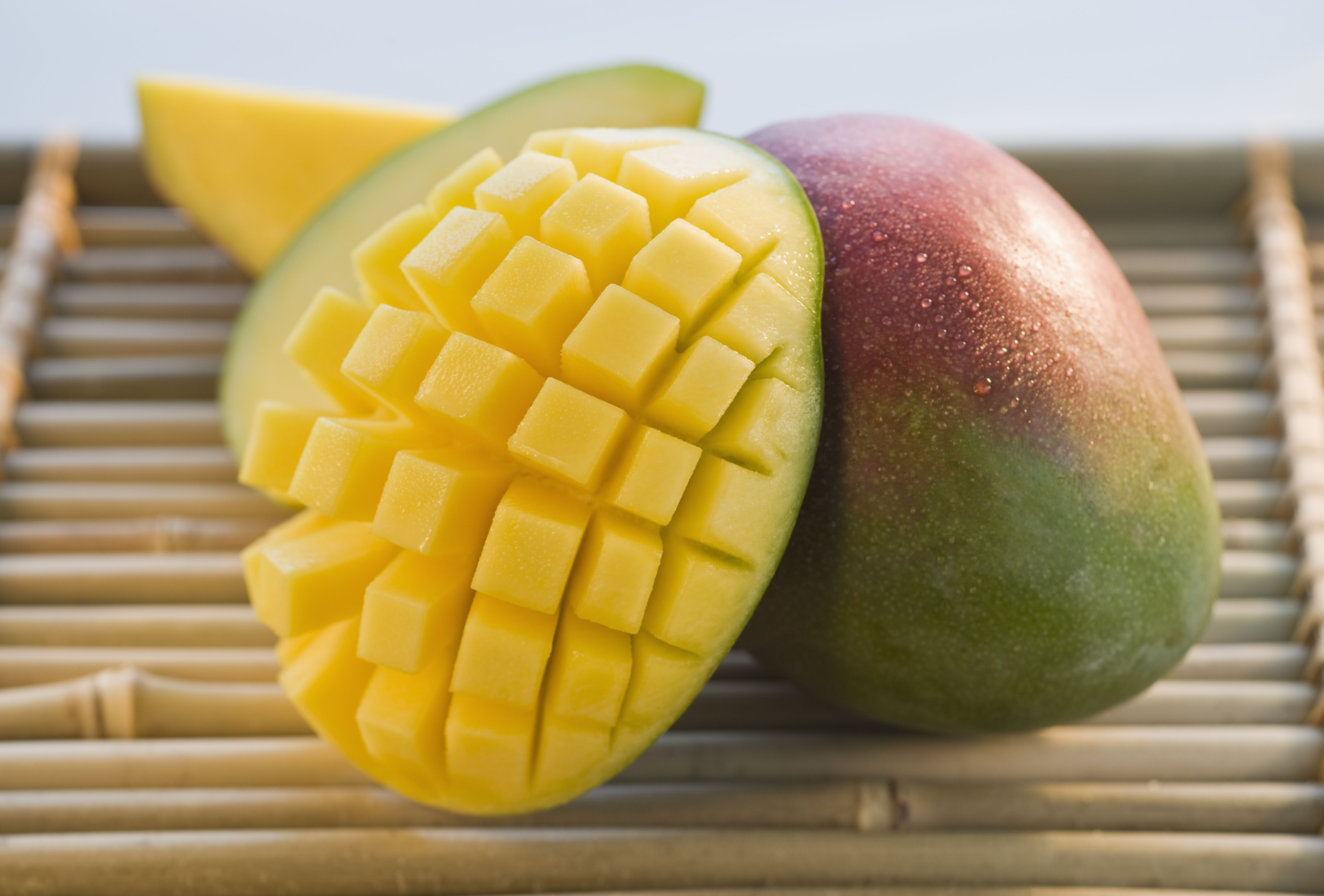Mango cut into a grid on a bamboo tray