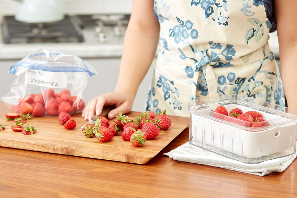cutting strawberries and placing them into boxes