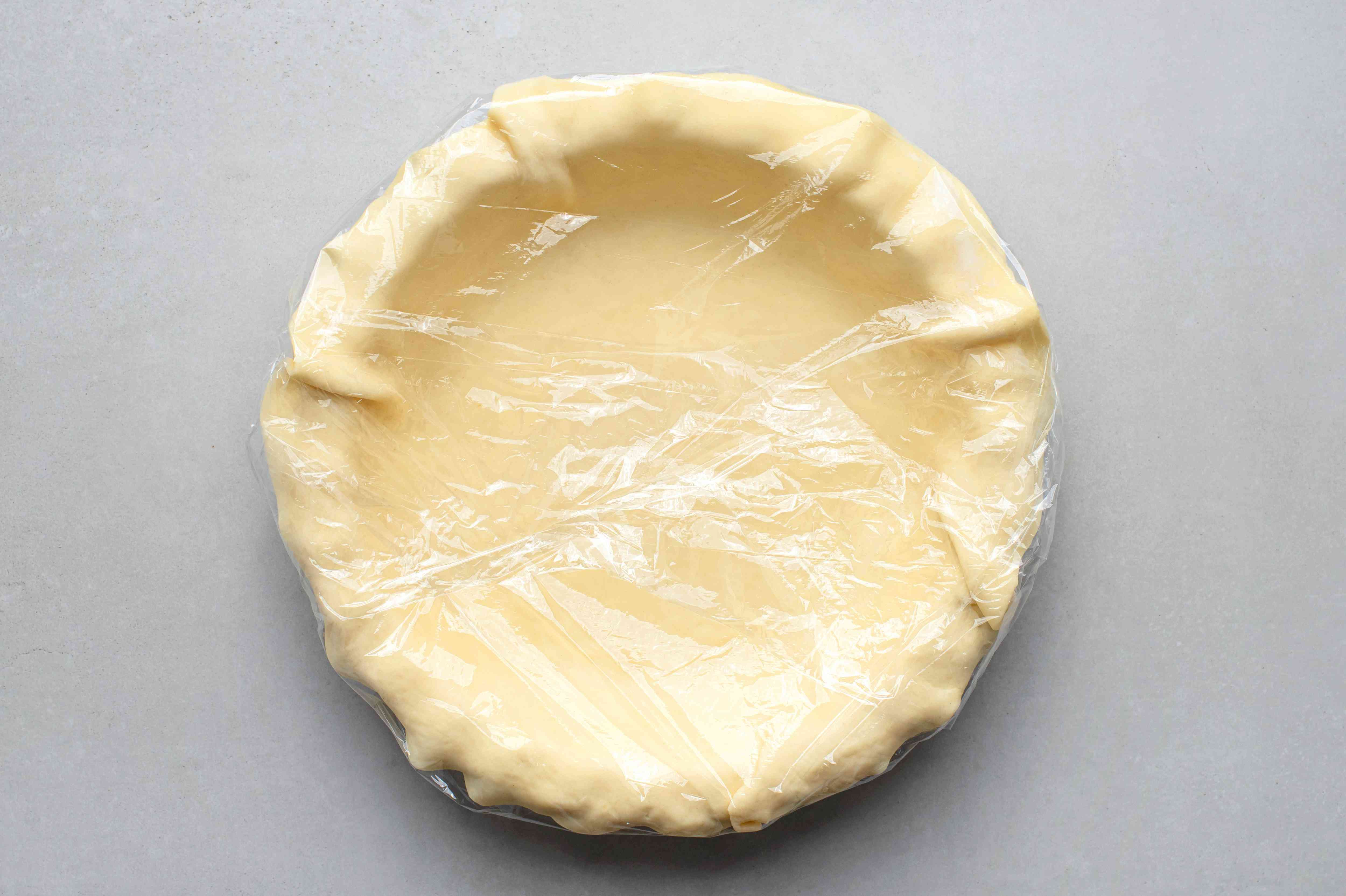 Line the pie pan with one crust, cover with plastic wrap