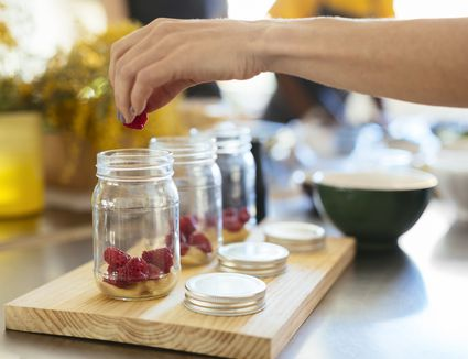 Close-up of woman in kitchen putting raspberry into jar - stock photo
