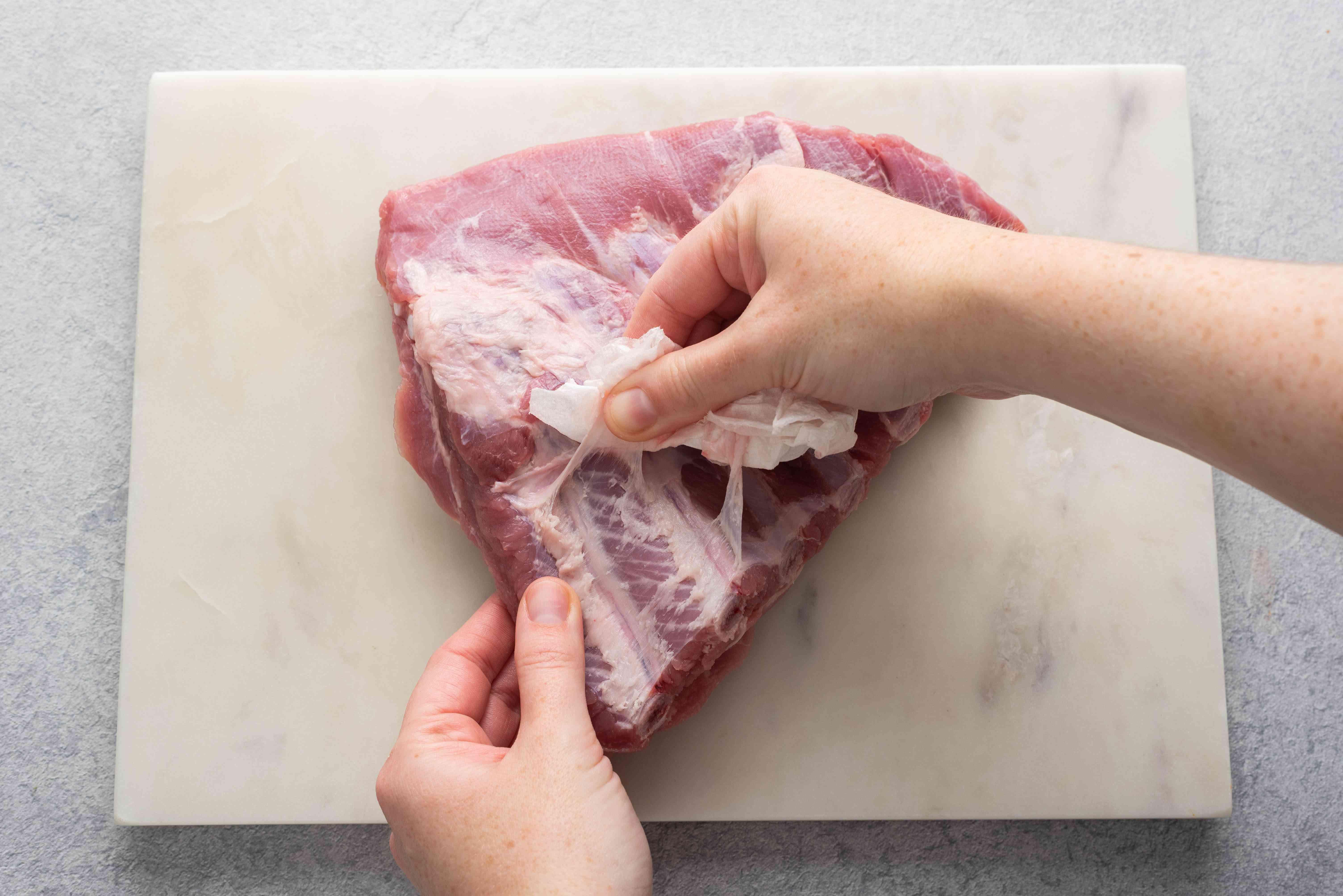 Peeling a sheet of silverskin from the ribs