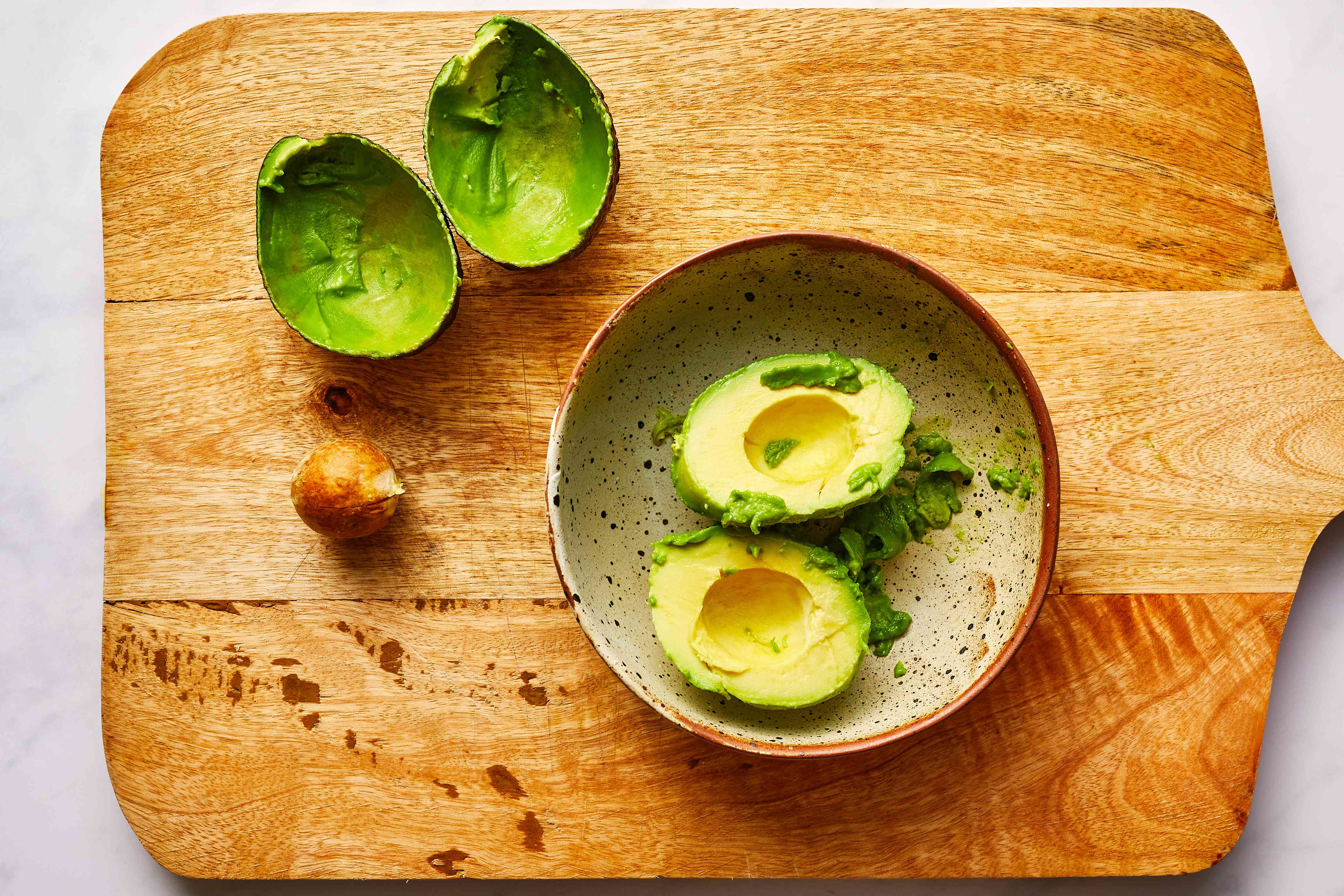 avocado peeled and seeded on cutting board resting in a bowl