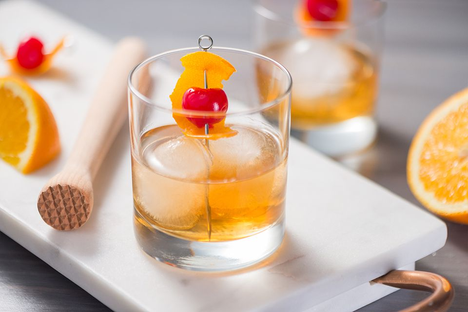 Classic old-fashioned on the rocks with an orange peel and cherry garnish