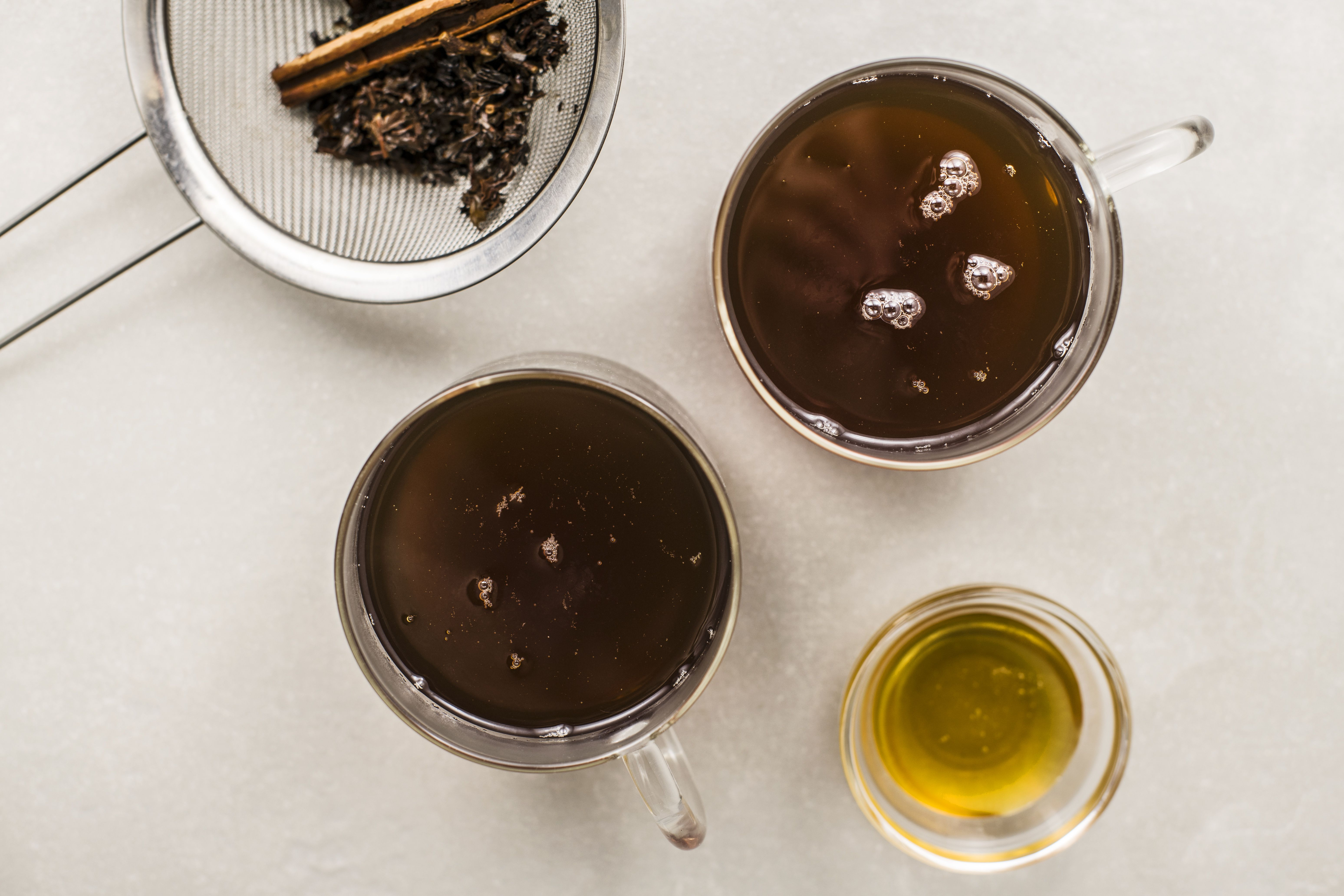 Tea strained with two mugs of tea and honey