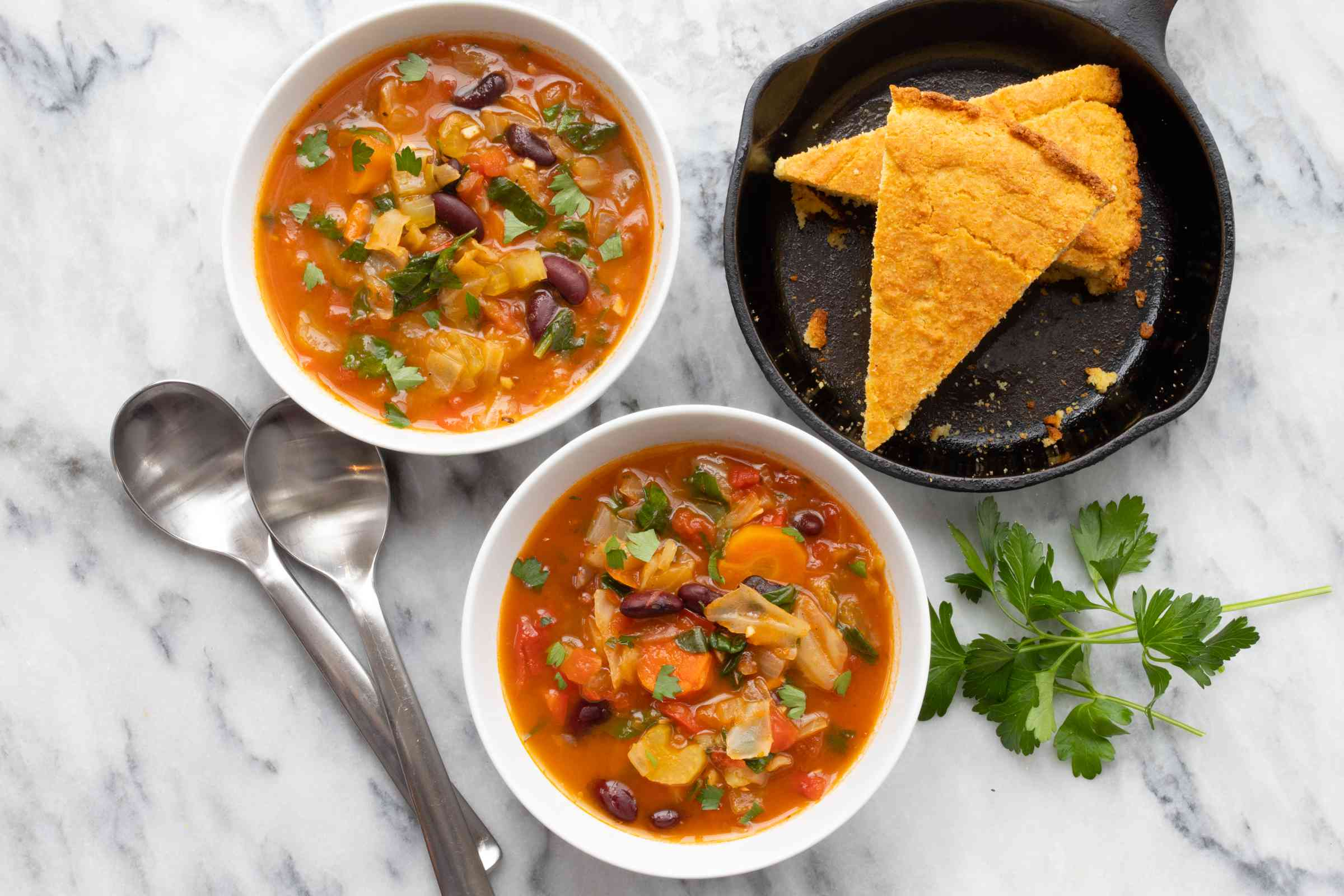 bowls of vegetable soup with cornbread