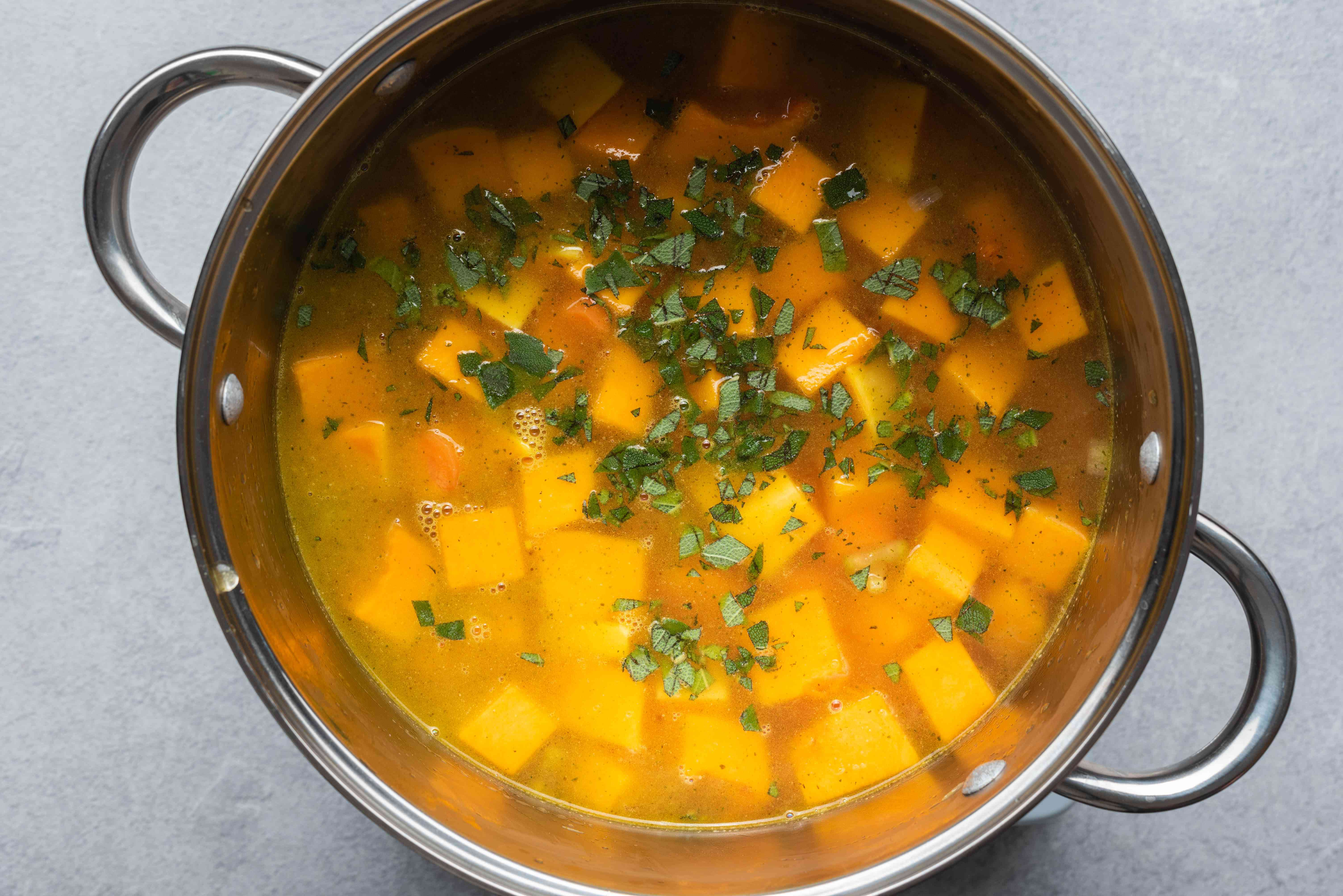 Add the chopped butternut squash and vegetable broth to the vegetable mixture in the pot