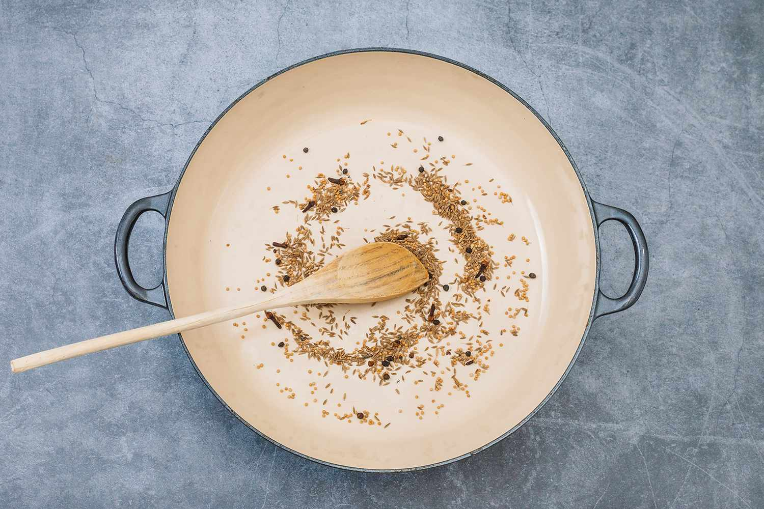 add the cumin seeds, mustard seeds, peppercorn, cardamom seeds, and cloves to a skillet