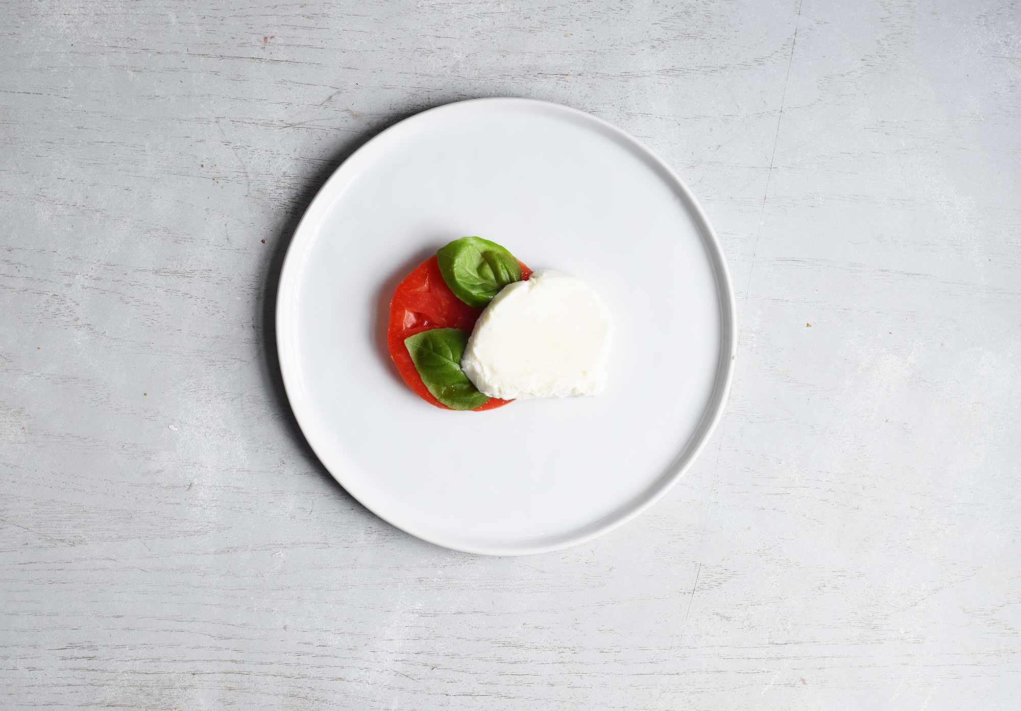 layering mozzarella cheese with tomatoes and basil