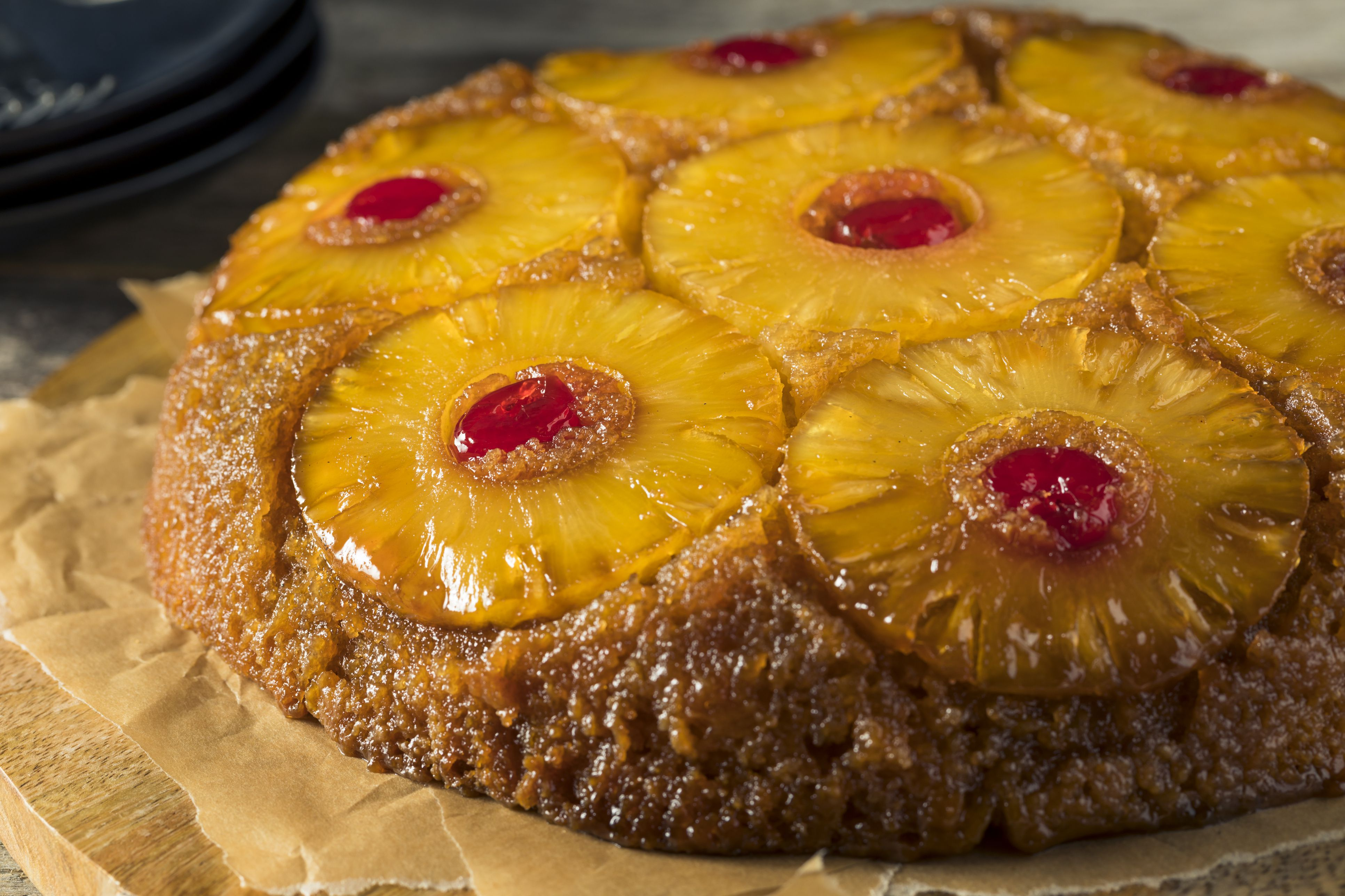 Sweet homemade pineapple upside-down cake on a wooden cutting board
