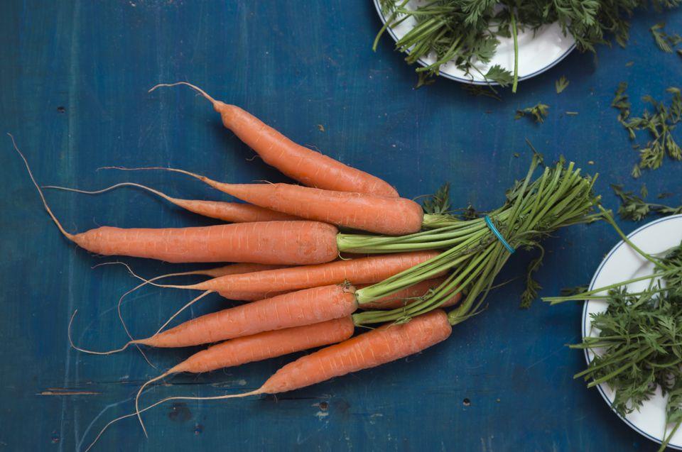 Fresh carrots on blue background
