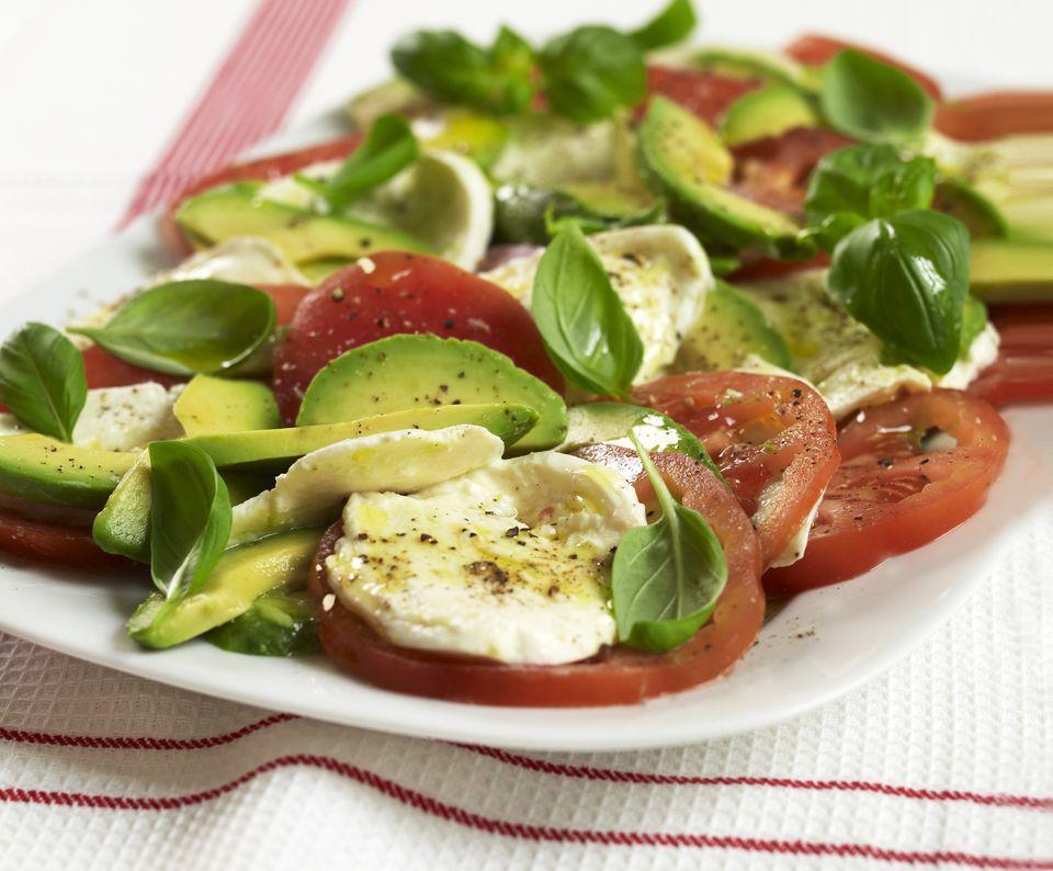 Tricolore avocado caprese salad with mozzarella, tomato and fresh basil