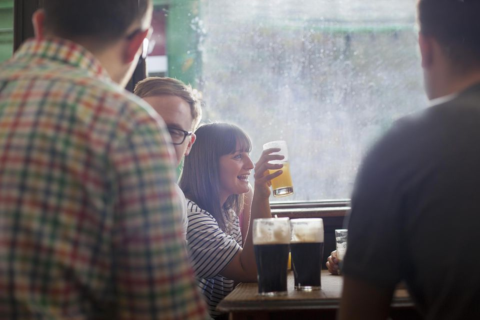 People sitting around table holding beer in glasses