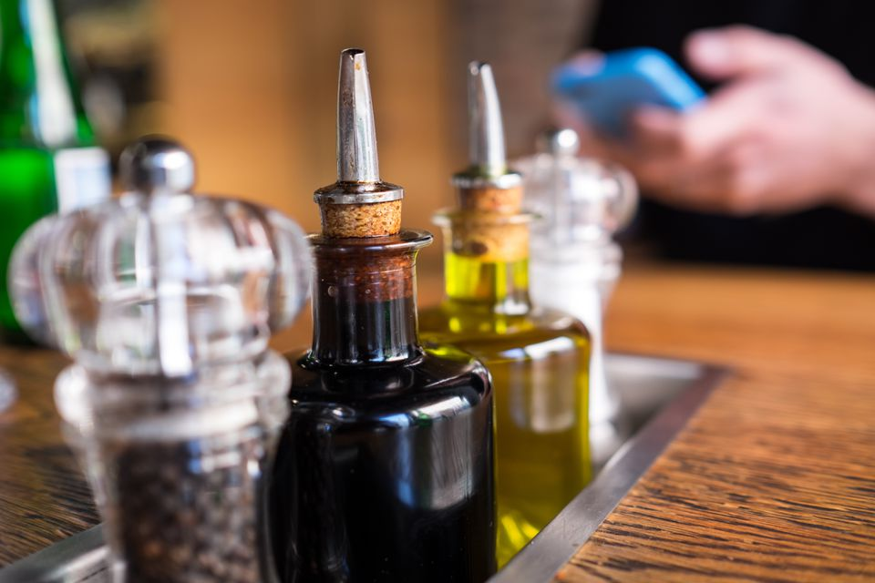 Close-Up Of Vinegar Bottles With Salt And Pepper Shaker On Table