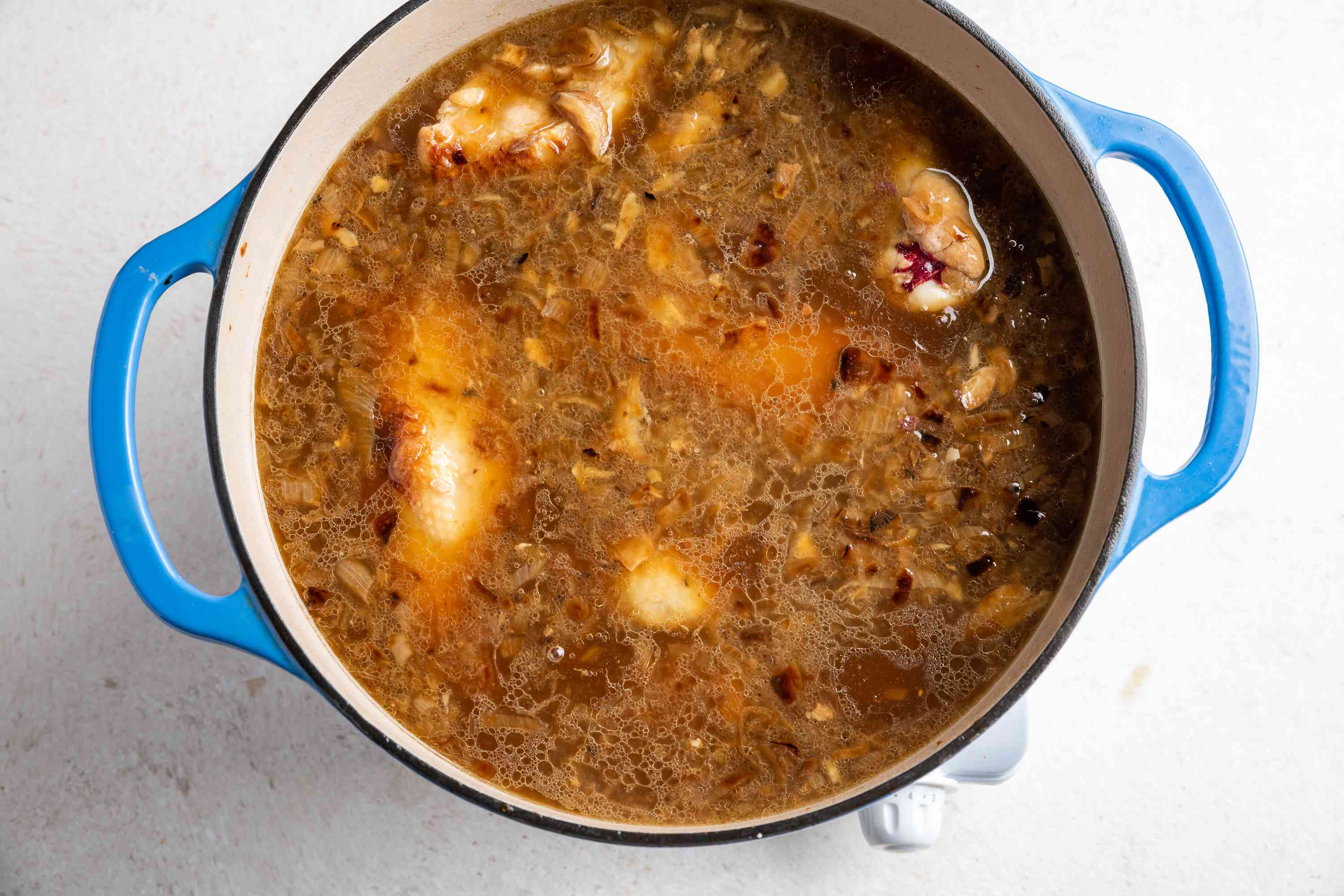 chicken with chicken broth cooking in a pot