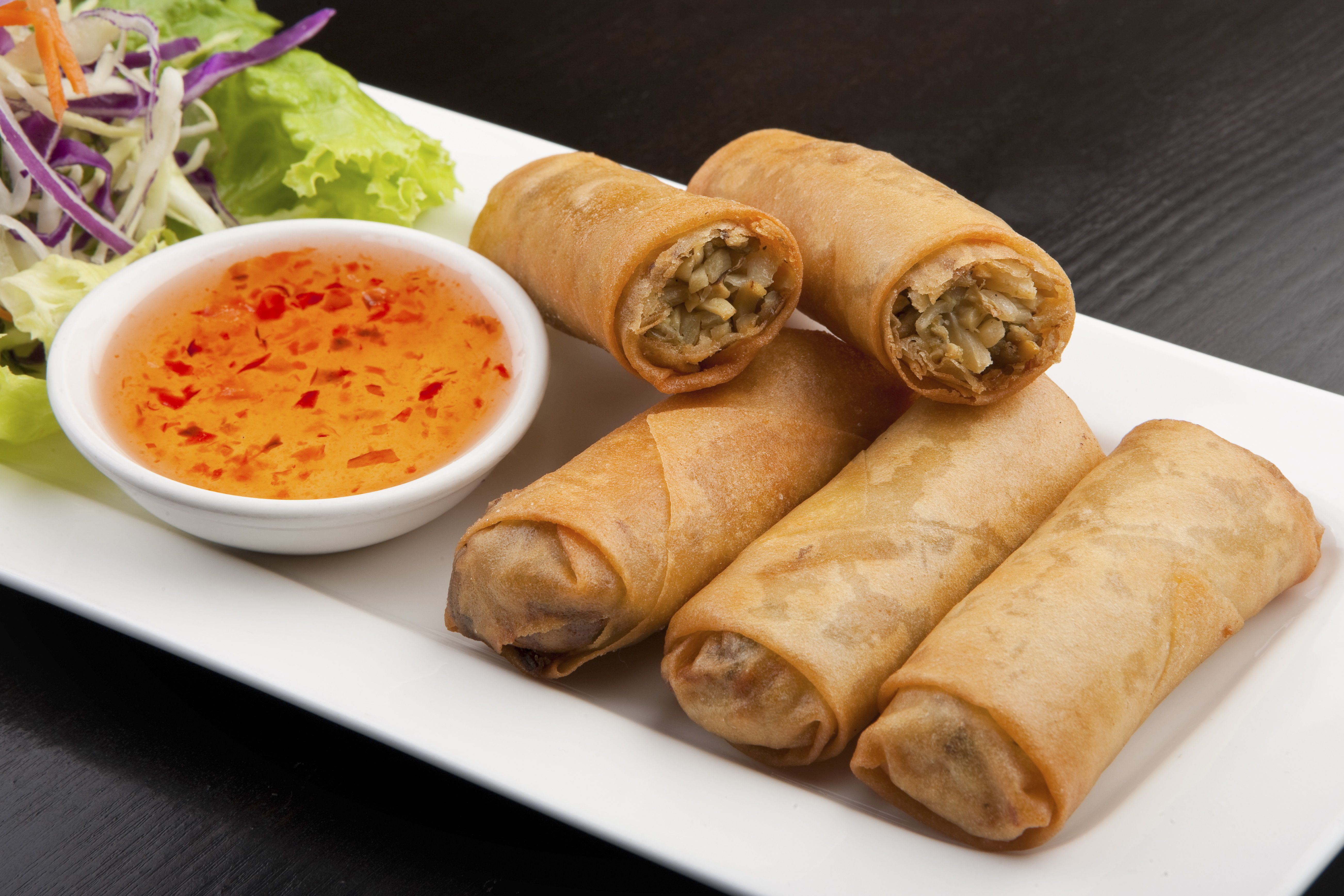 Plate of spring rolls, sauce and salad