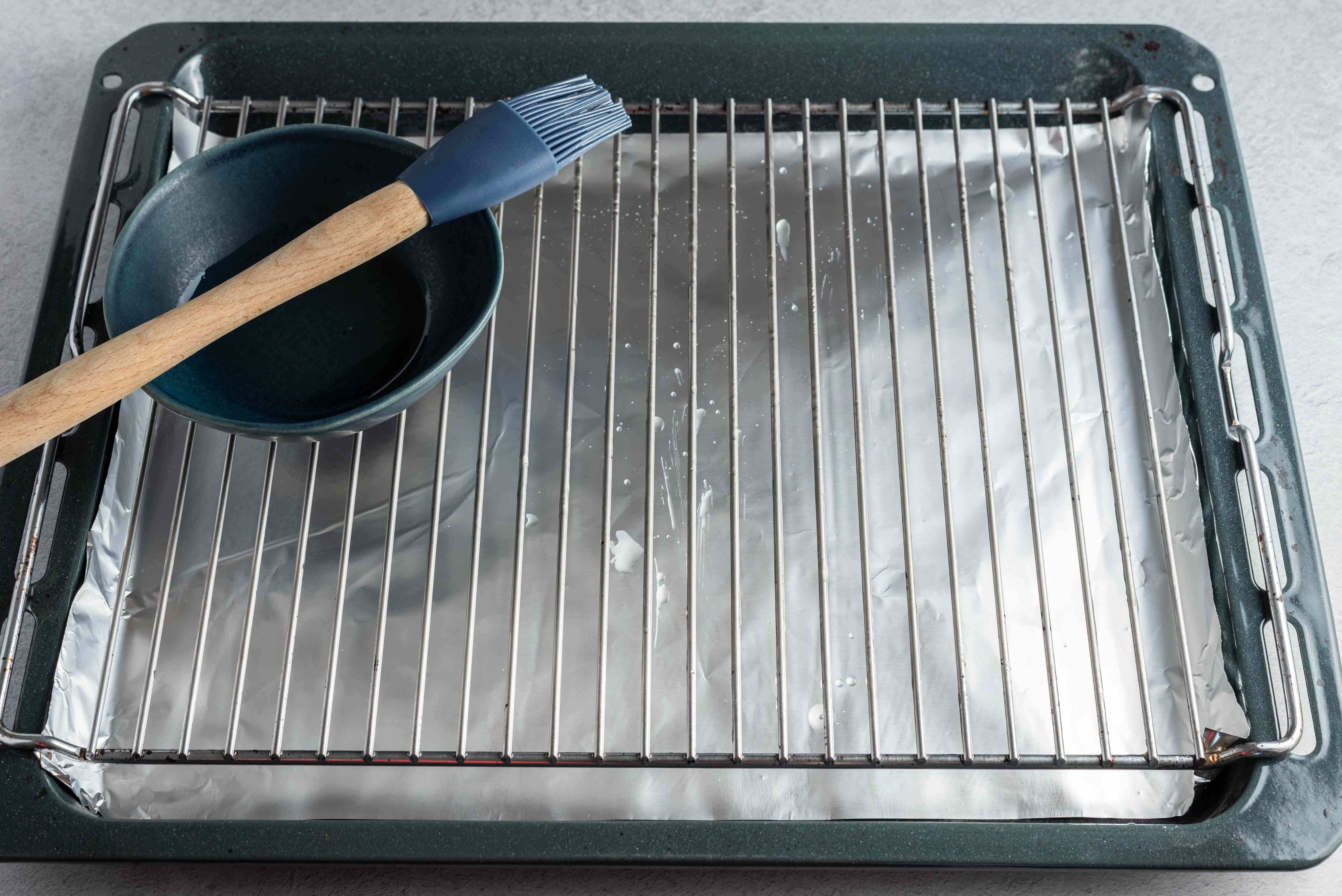 Broiler pan lined with foil and rack brushed with oil