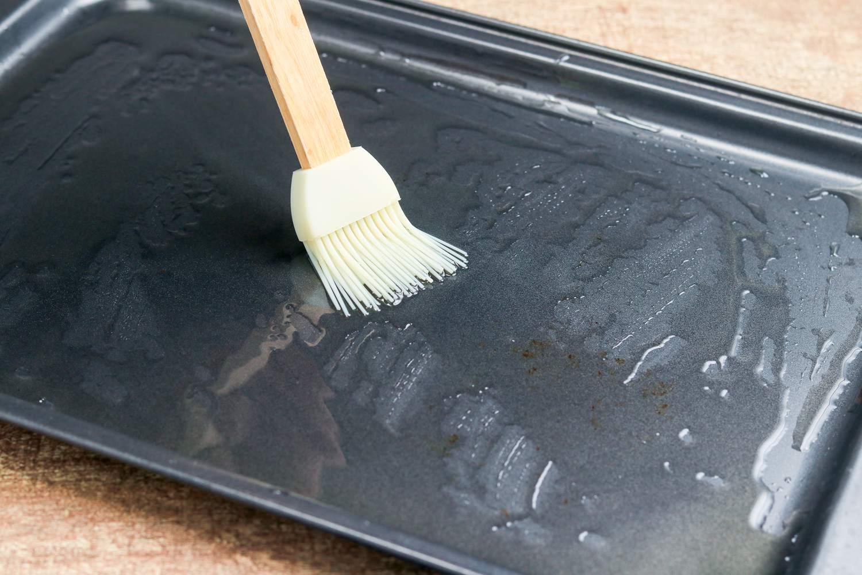 Brush spreading oil on pan