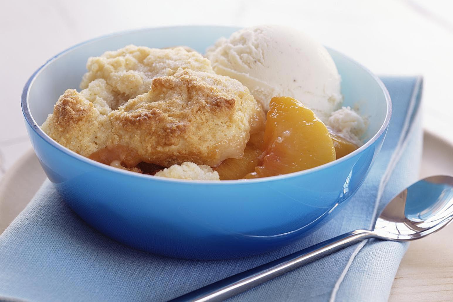 Peach cobbler a la mode in a blue bowl