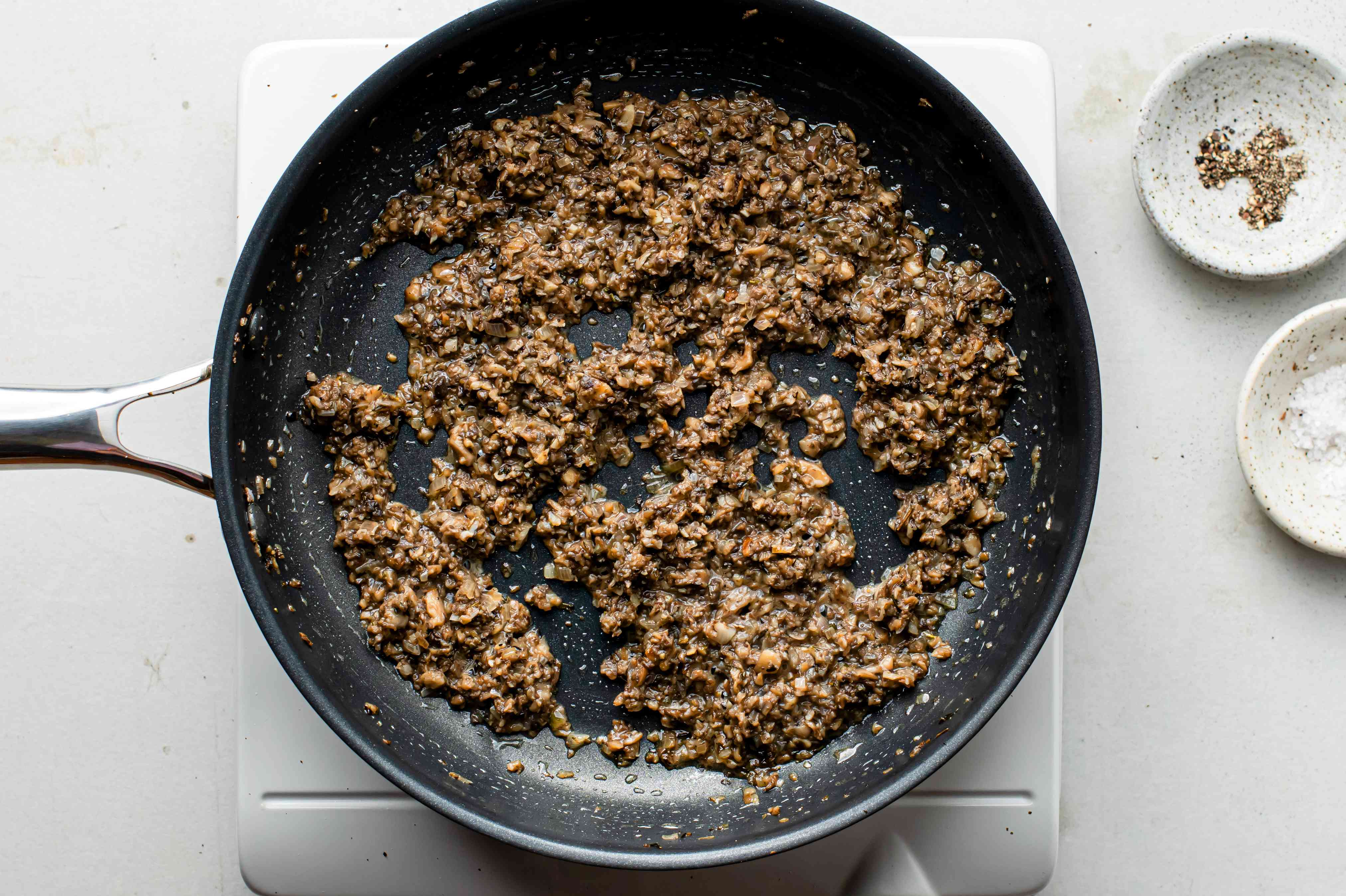 Cooked mushroom duxelles in a black nonstick pan