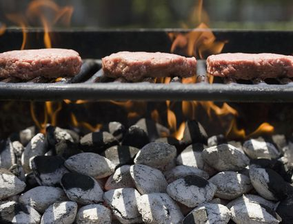 Grilling patties on a charcoal grill