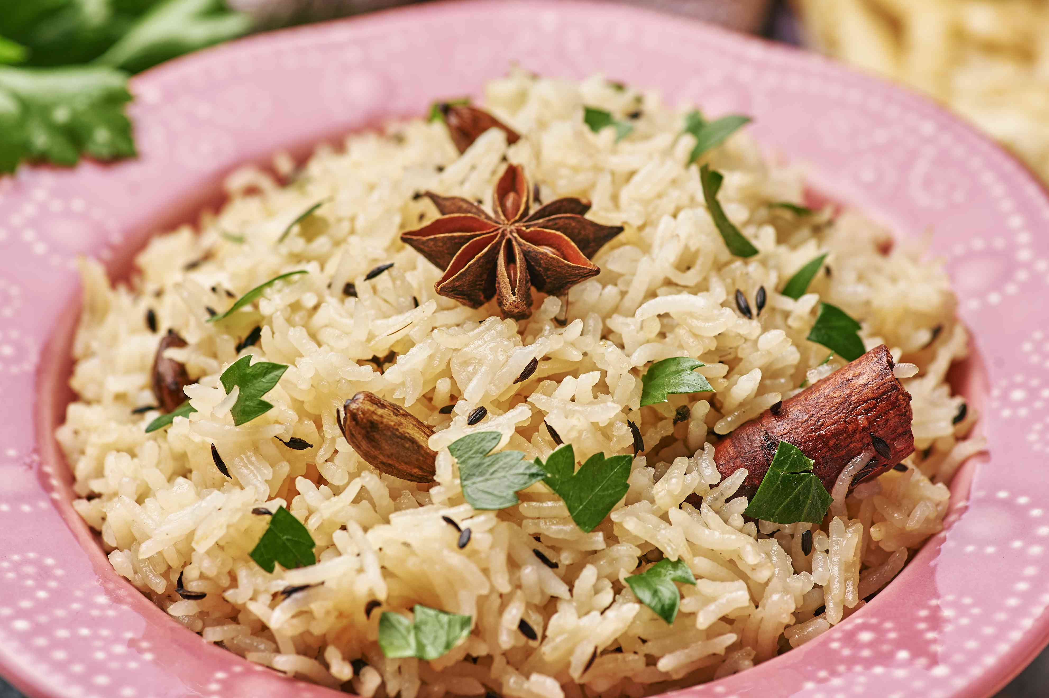 Jeera Rice in pink plate at dark bacgkround.