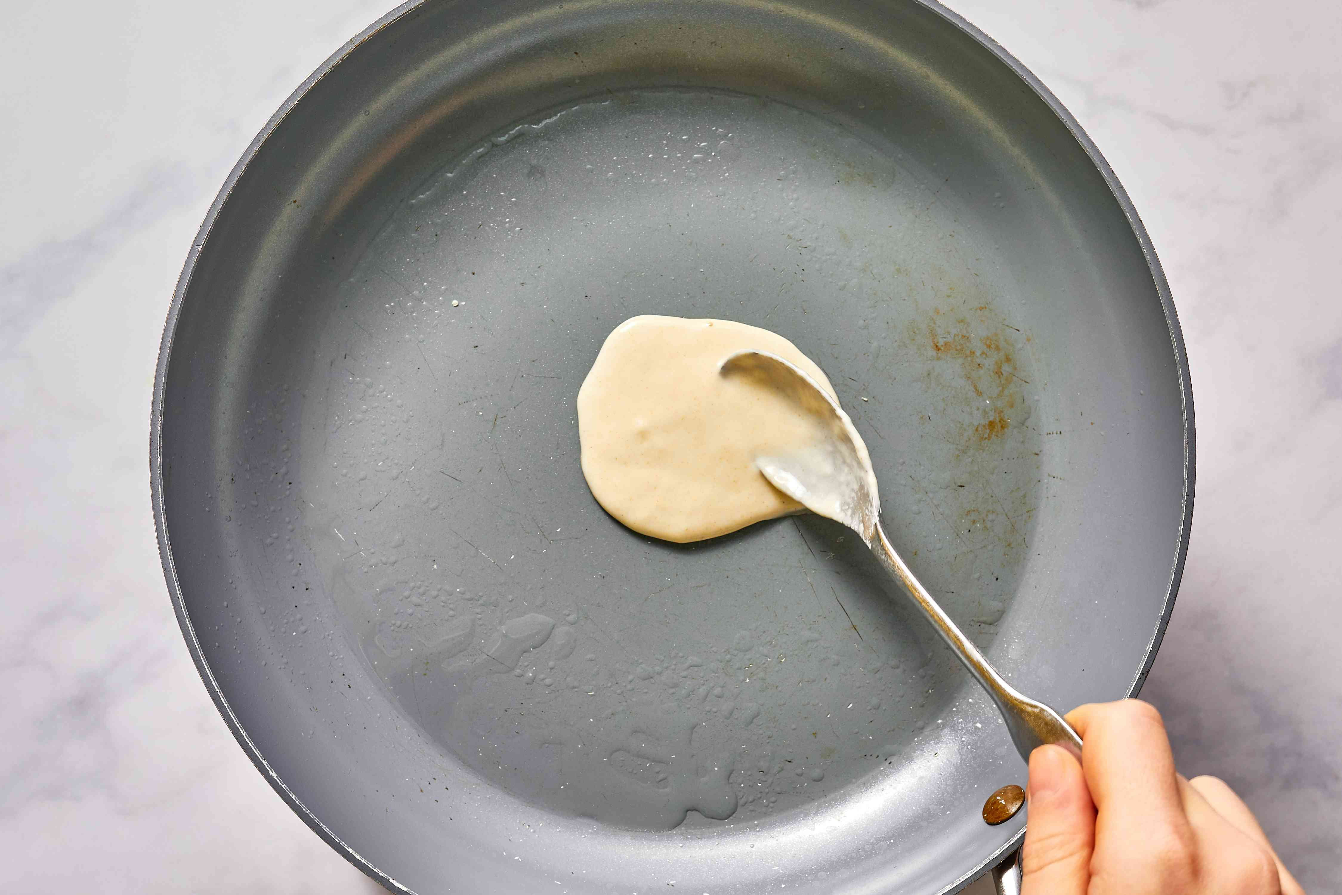 Adding spring roll wrapper batter to hot pan