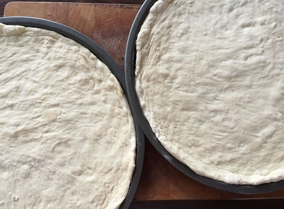 High Angle View Of Pizza Dough In Plates On Wooden Table