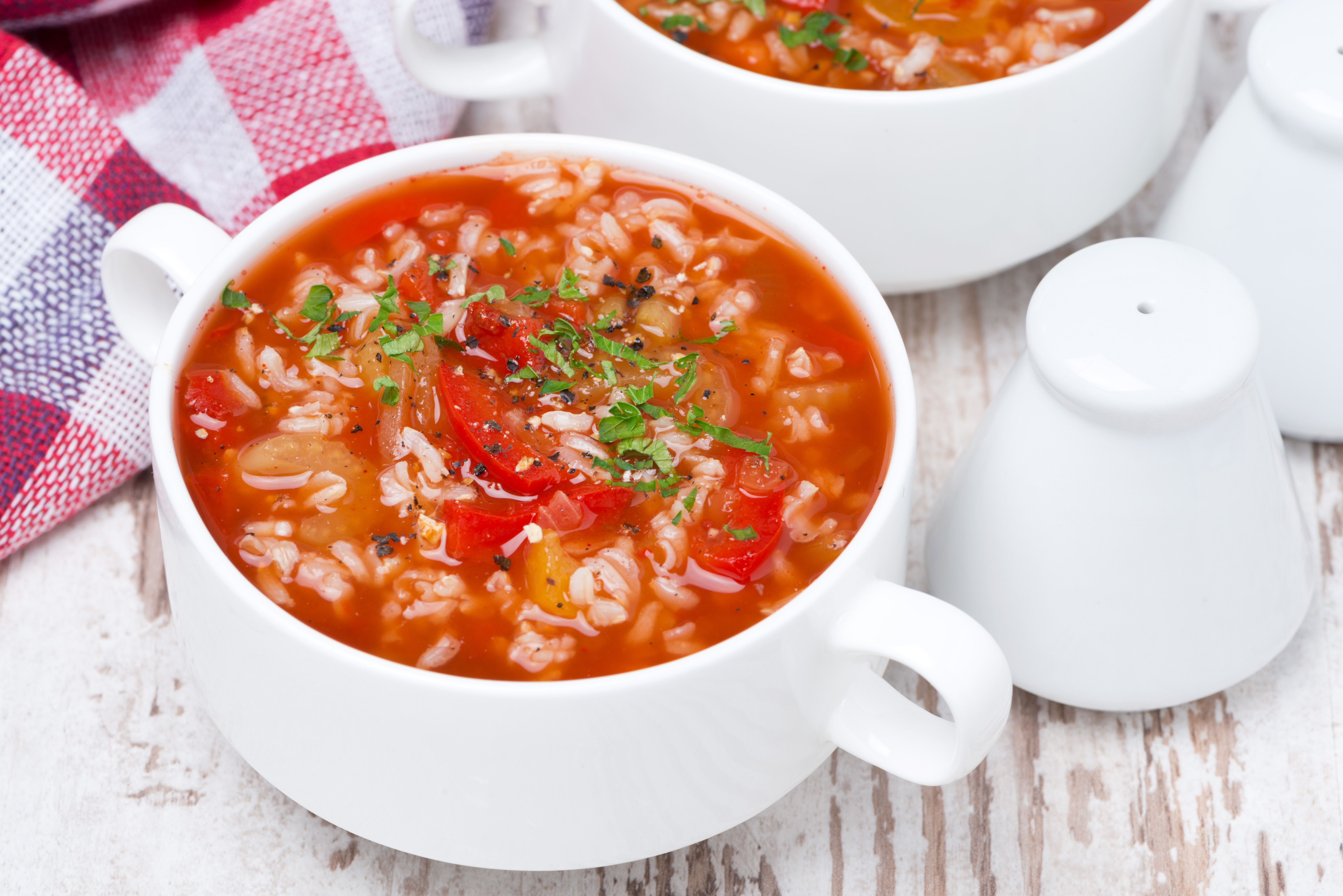 Tomato soup with rice and vegetables in bowl, top view