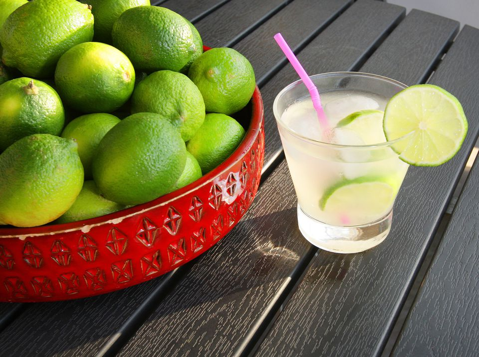 Limeade next to a bowl of limes