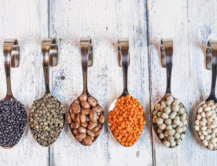 Row of spoons with different dried pulses