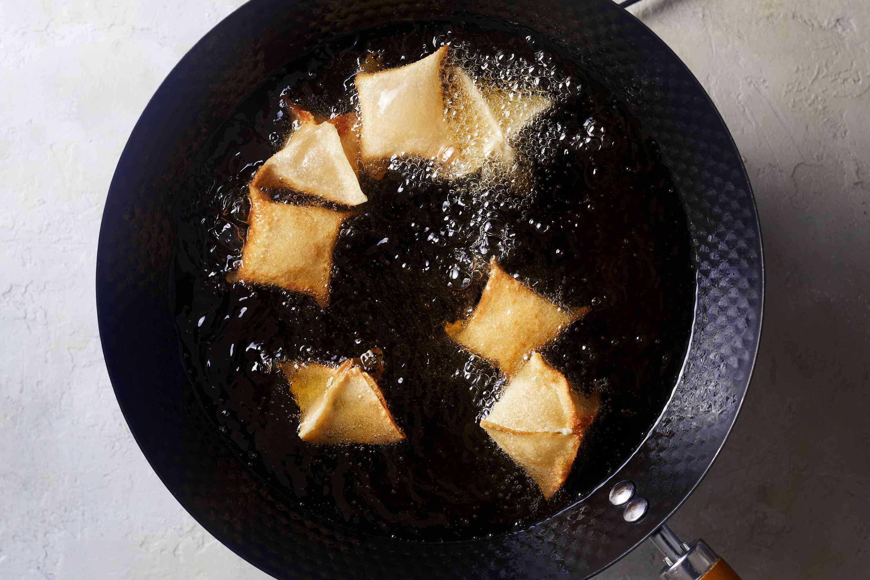crab rangoon cooking in a wok with oil