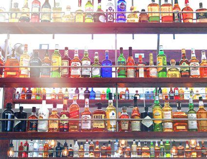 Liquor bottles lined on multiple shelves