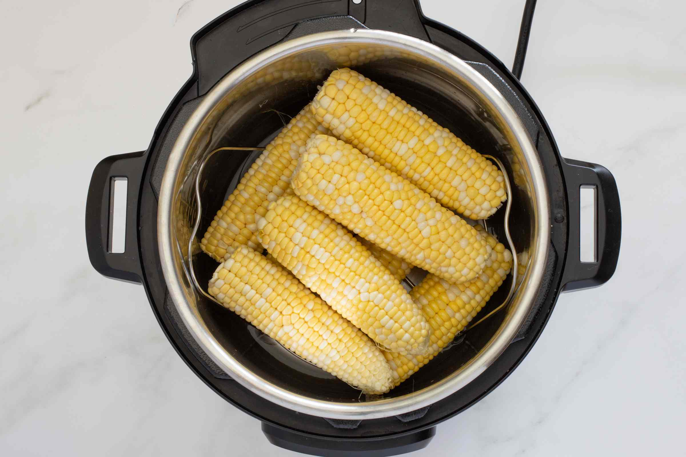 Corn on the cob stacked in the Instant Pot.