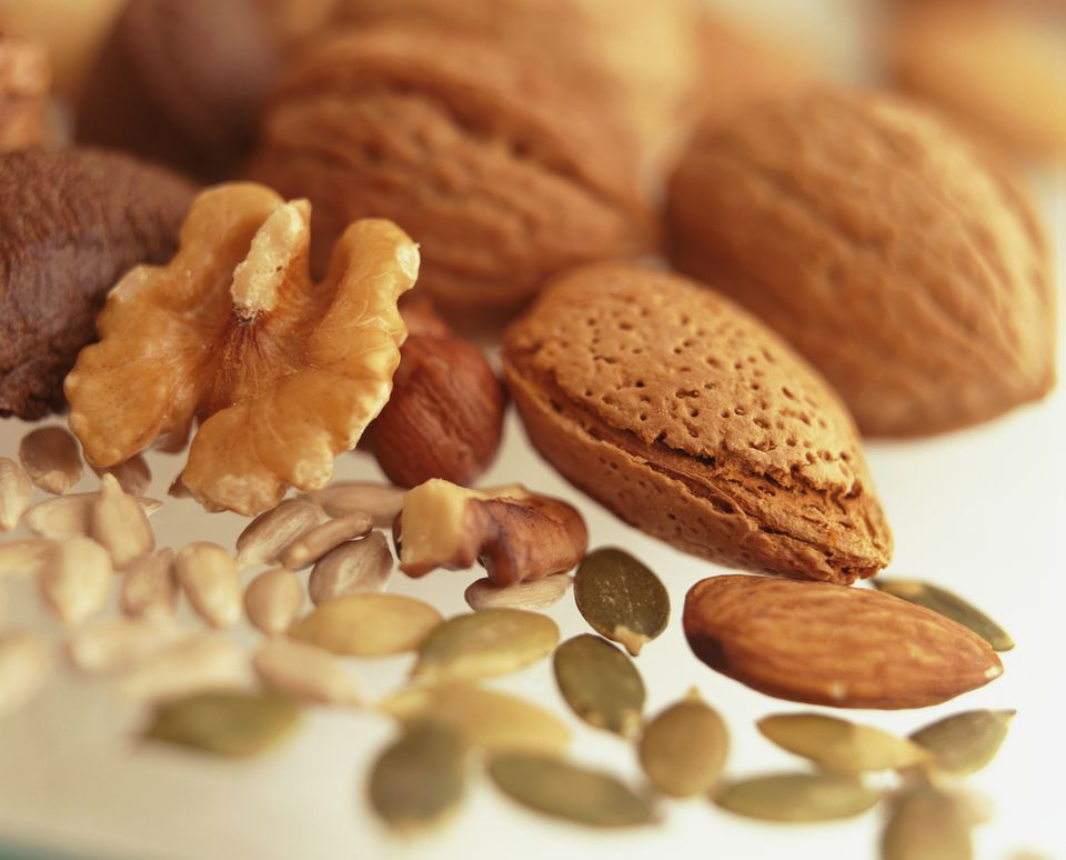 Group of raw nuts and seeds including walnut, almond, pinenuts, pumpkin, sunflower seeds.