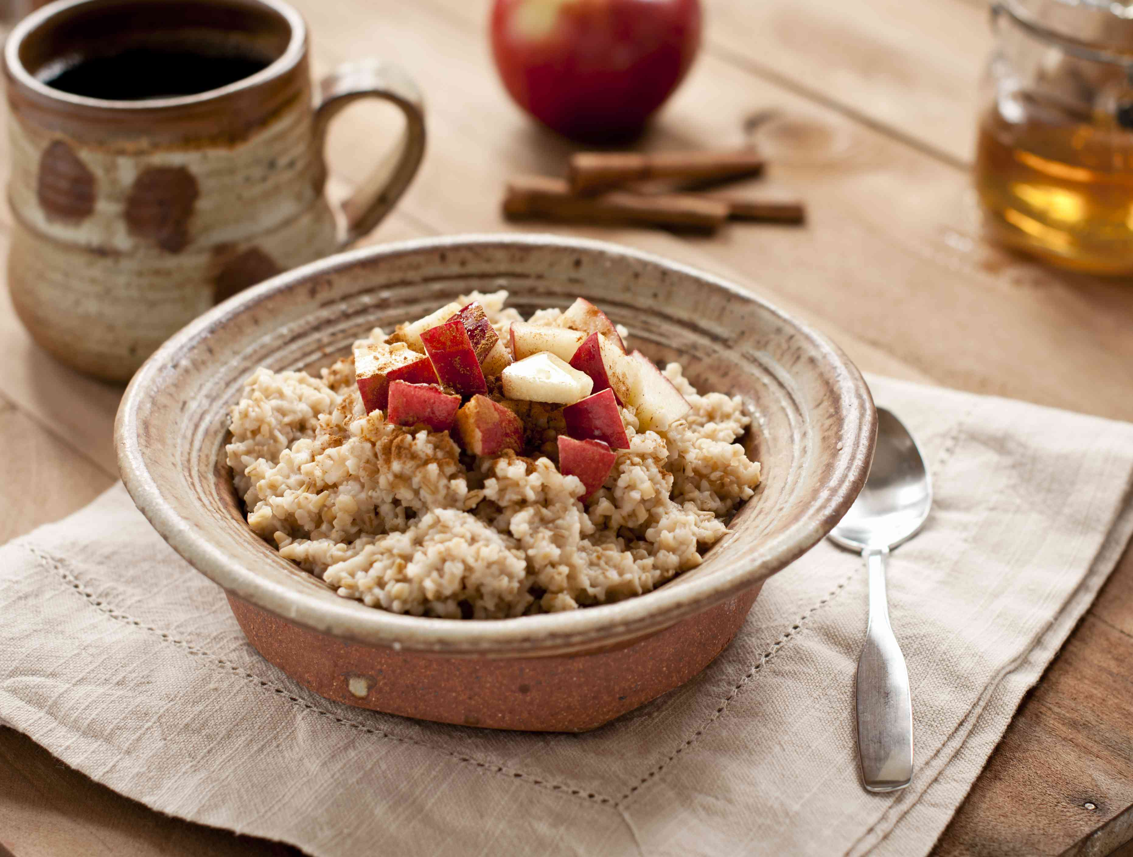 Breakfast made of oatmeal with apples, honey and cinnamon