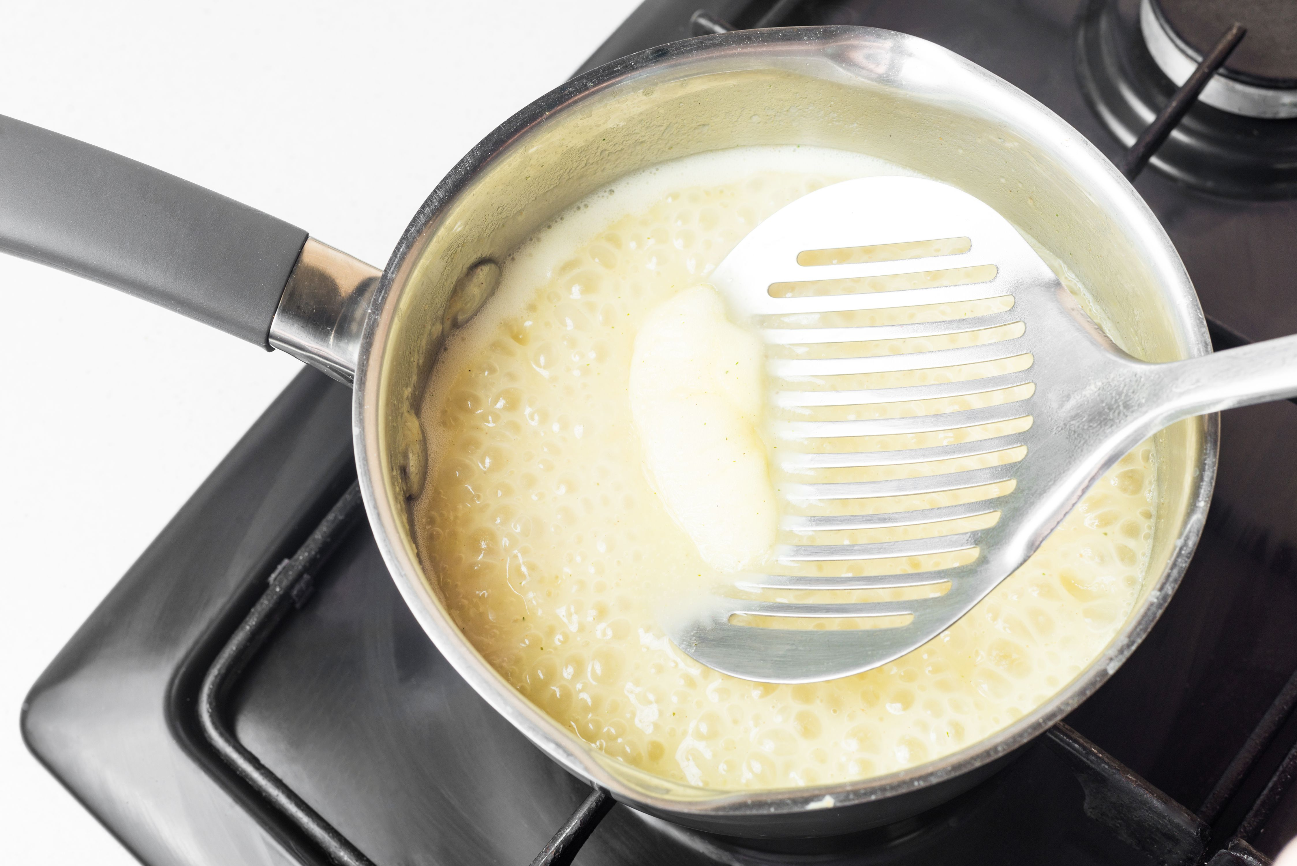 Simmer roux and use ladle to remove impurities
