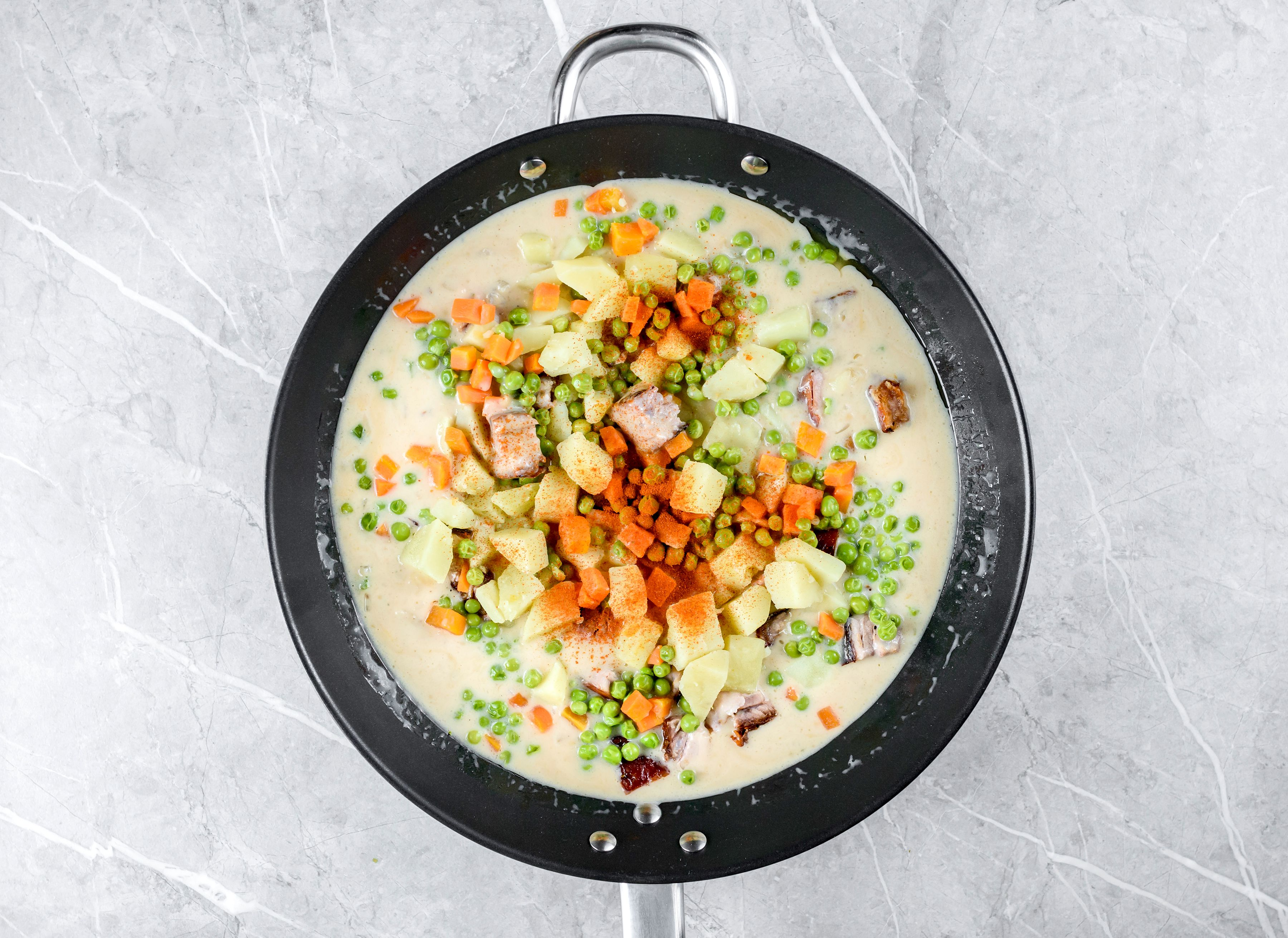 Add the pork, diced potato, peas, carrots, and paprika