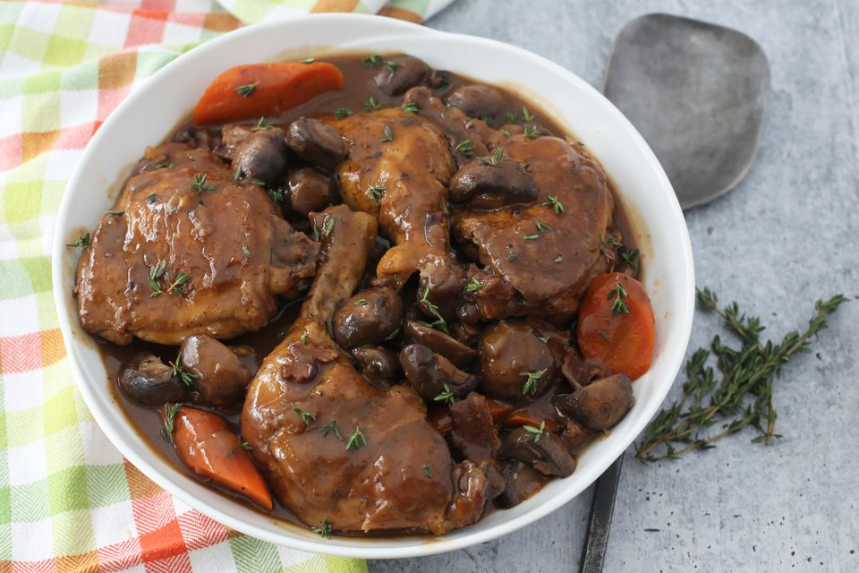 Instant Pot coq au vin in a bowl with thyme sprigs.