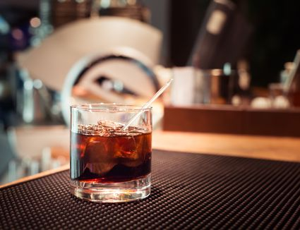Glass of Black Russian on bar.