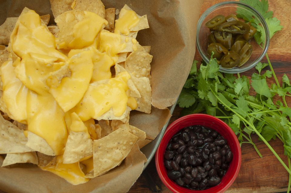 nacho cheese sauce on tortilla chips with black beans