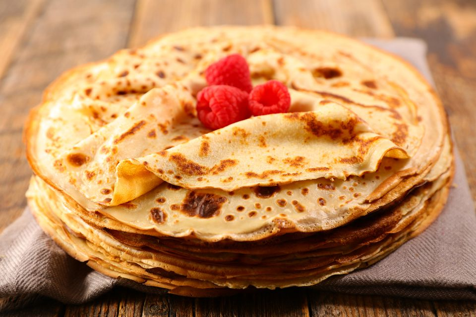 stack of crepes topped with raspberries