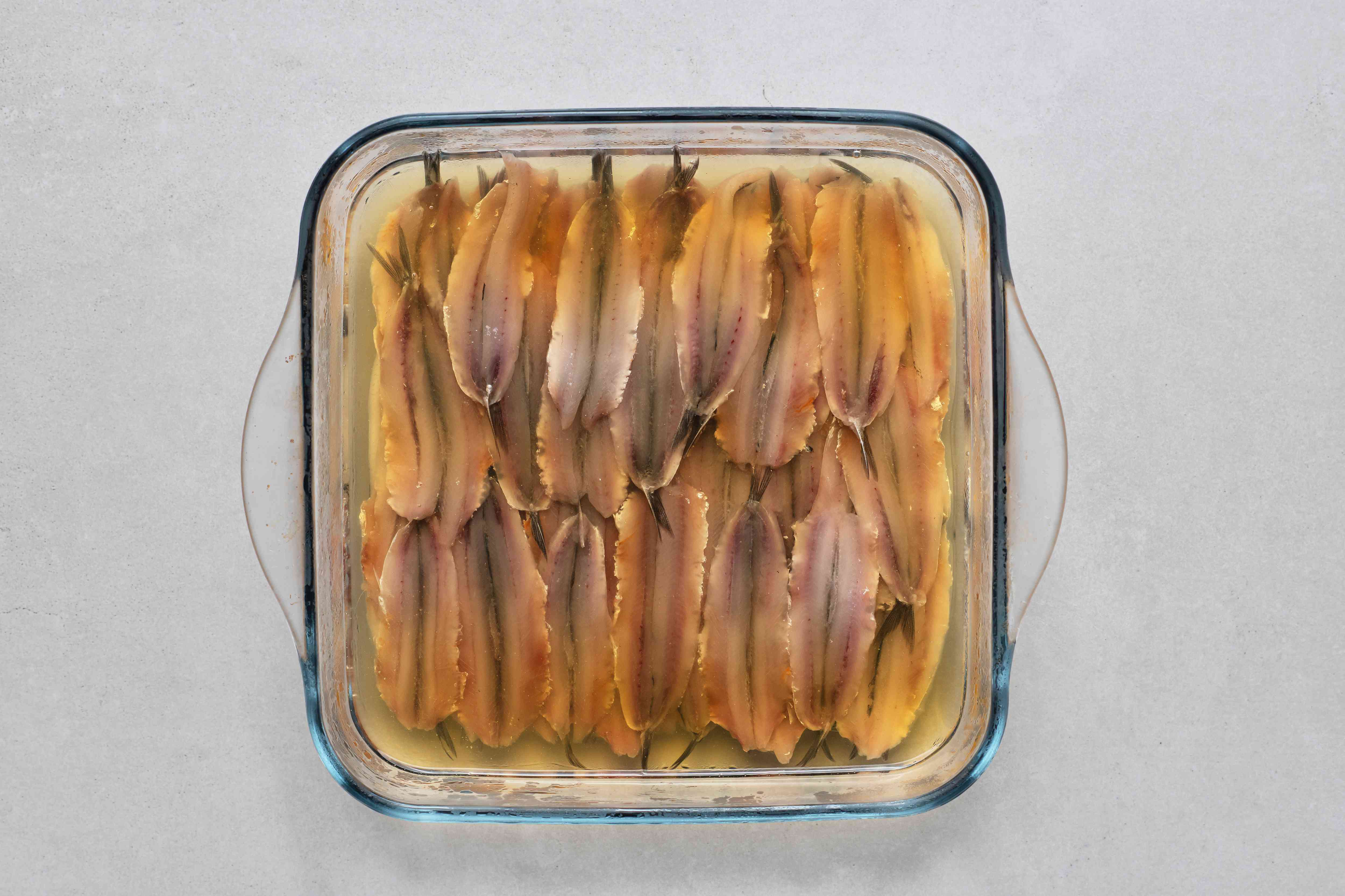 vinegar in a bowl with frozen anchovies in a glass baking dish