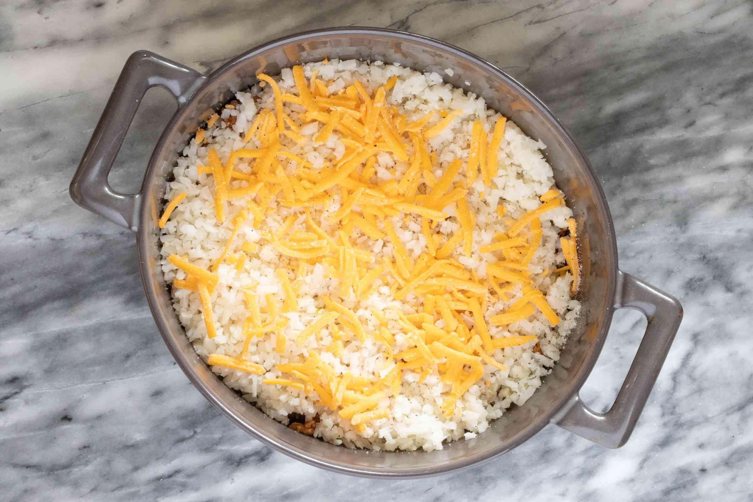 Cauliflower rice layer on the ground beef layer.