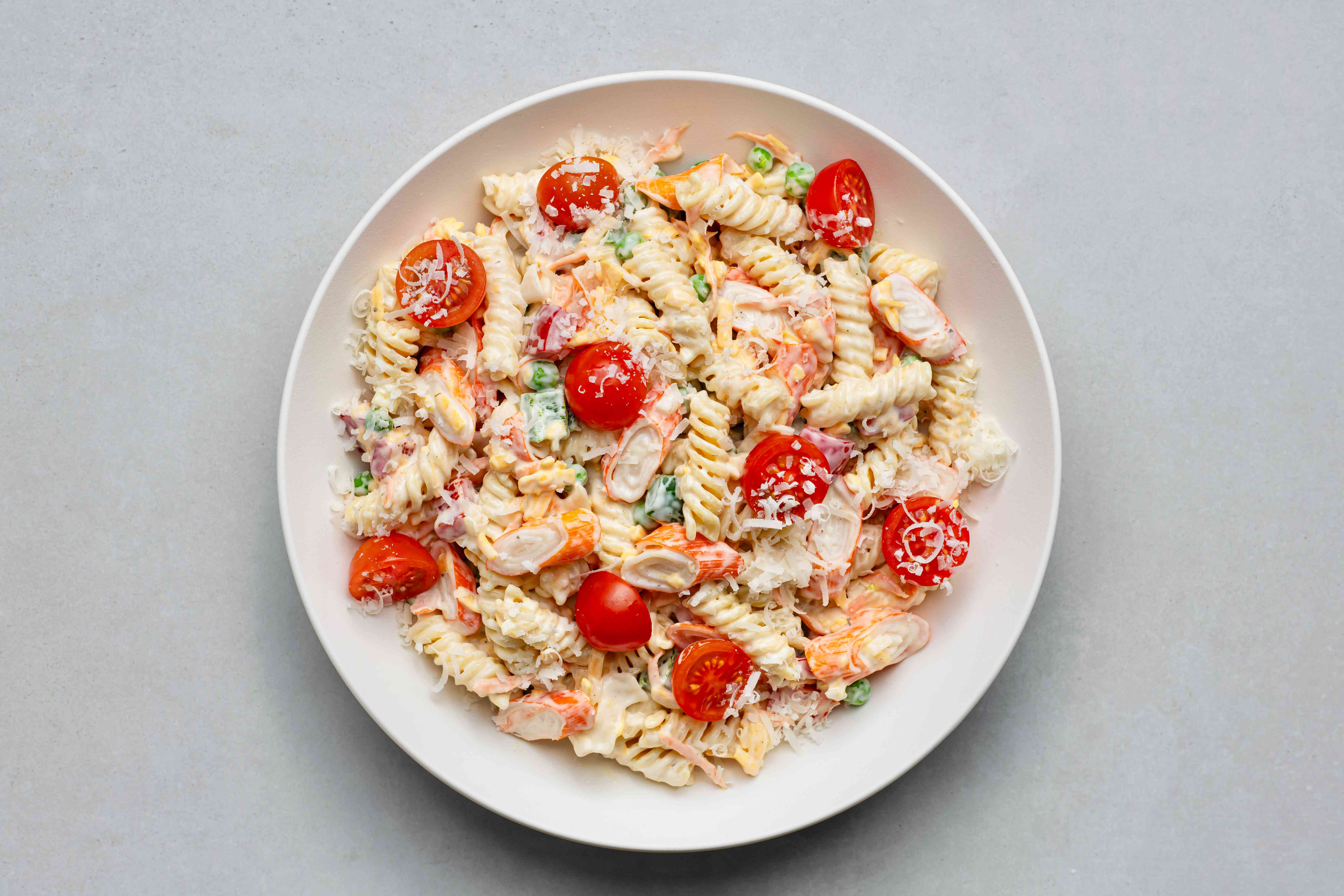 Summer Seafood Pasta Salad, topped with cheese and tomatoes