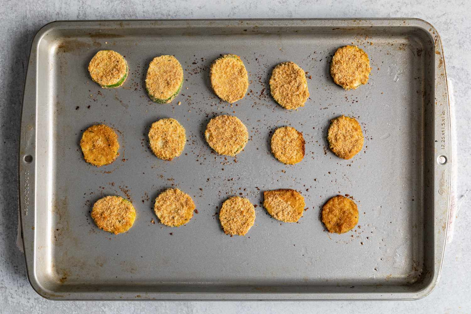 baked breaded zucchini pieces on a baking sheet