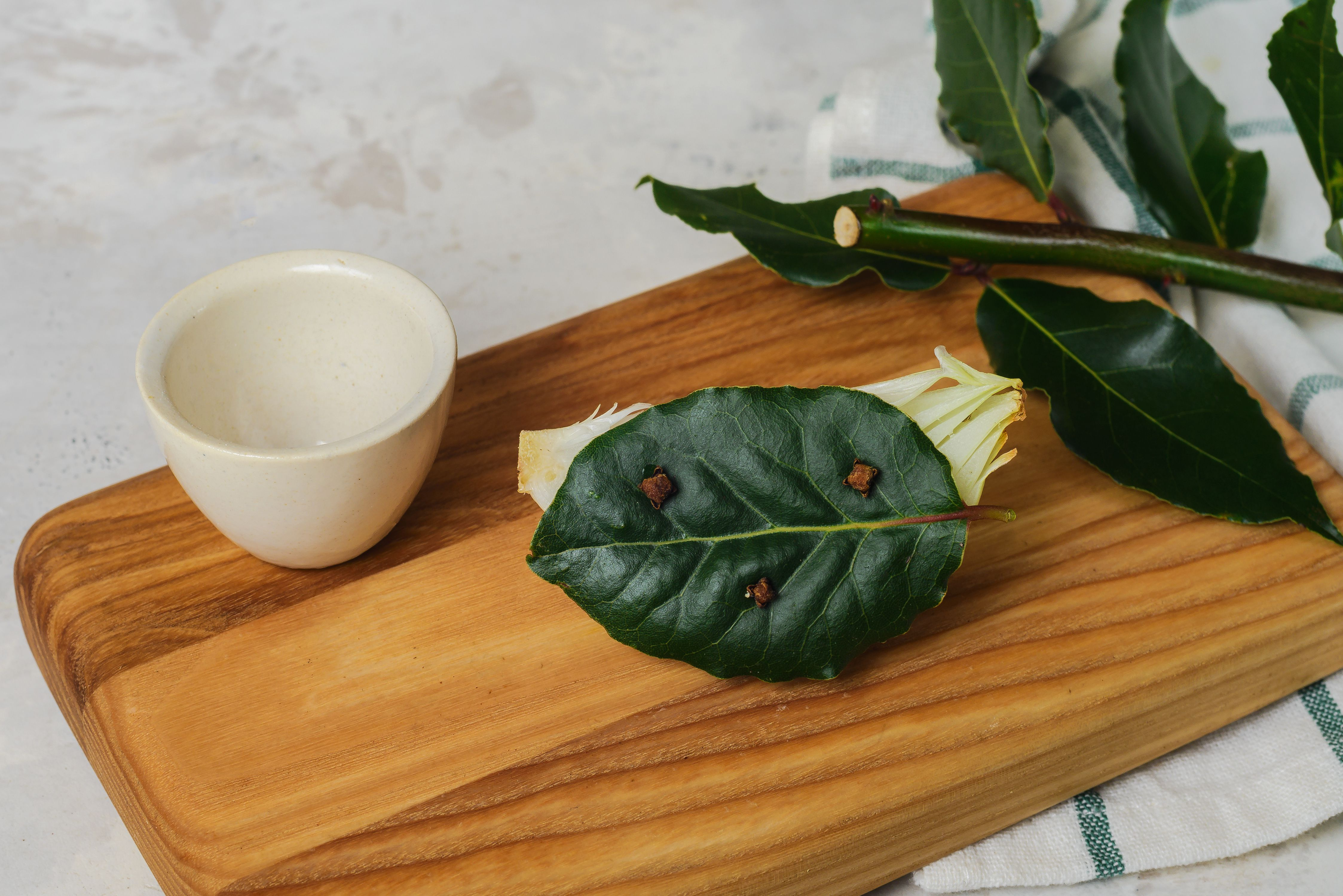 Attach bay leaf with cloves to onion