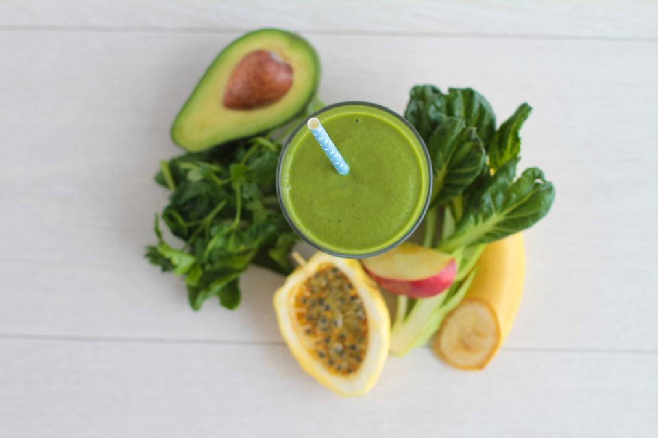 Green smoothie next to avocado, greens, apple and banana