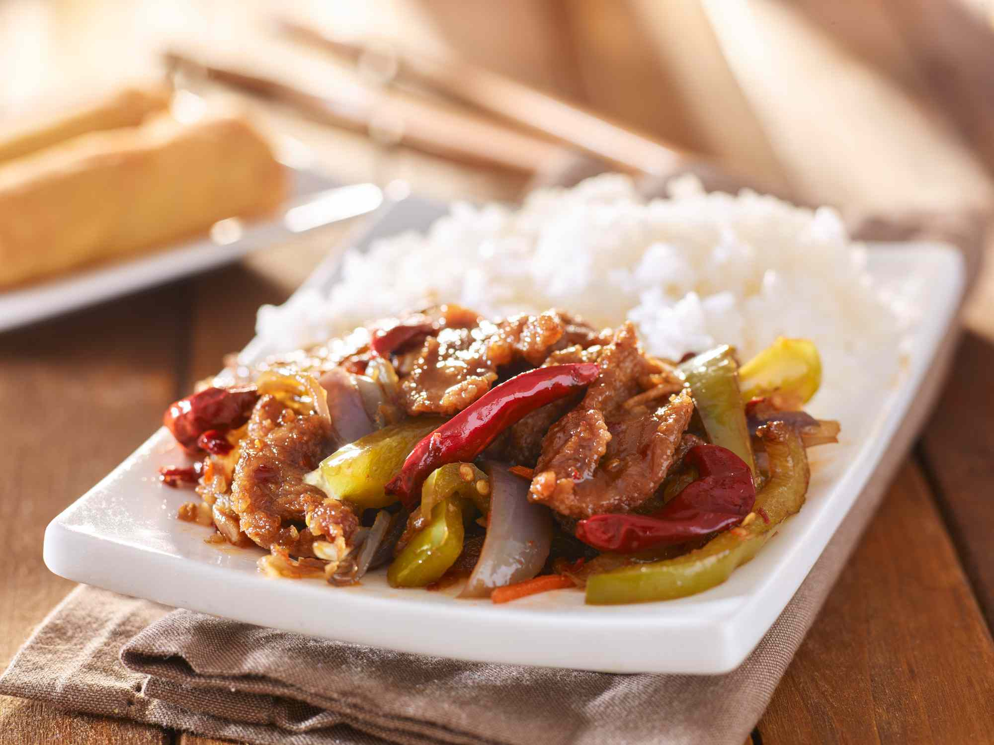 chinese szechuan beef with rice on plate