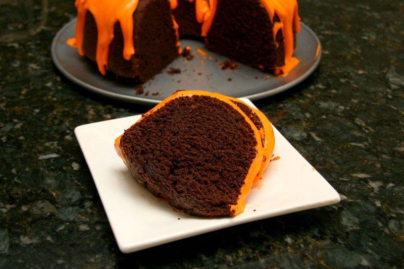 Slice of pumpkin bundt cake with orange frosting on a plate